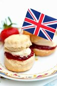 Two scones with strawberry jam, custard cream and a Union Jack