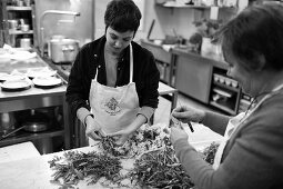 Women sorting herbs in kitchen