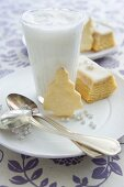 Hot milk with cinnamon and honey, a slice of cake and a biscuit