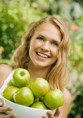 Young woman holding bowl of apples