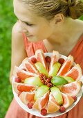 Woman holding plate full of fruit slices, high angle view