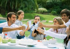 Family clinking cups over birthday cake