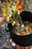 Gemüsesuppe im Kessel am Lagerfeuer zubereiten