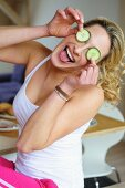 Young woman covering her eyes with cucumber slices