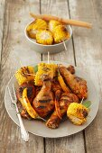 A grill platter with chicken legs, corn cobs and chilli peppers