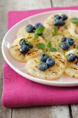 Grilled pineapple slices with honey and blueberries