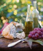 Rustikales Picknick mit Brot, Trauben und Wein