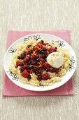 A sweet pasta dish with warm berries, vanilla ice cream and cinnamon