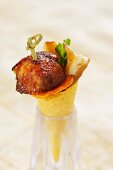 A wafer cone filled with chicken wings and porcini mushrooms