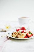 Strawberry Crepes on a Plate with Fork and Knife; Cup of Coffee