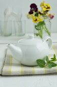 A white teapot with cutlery and pansies in the background