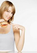 Woman holding up and pointing to sandwich