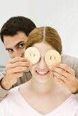 Young couple, man holding slices of fruit over woman's eyes