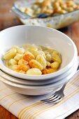 Bowl of potato gnocchi with fontina, gorgonzola, and taleggio sauce topped with parmesan