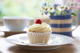 A white chocolate cream and raspberry cupcake