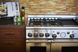 Contemporary stainless steel stove oven with tile backsplash