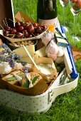 A picnic hamper with cheese, crackers, marshmallows, cashew nuts and cherries