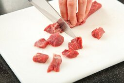 Cutting Lamb into Cubes on a Cutting Board