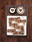 Domino tiles made of brownies, and two cups of cappuccino