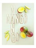 Fresh mangos next to lettering