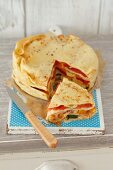 Pancake tart with cheese and vegetables, sliced