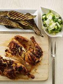 Grilled Chicken on a Cutting Board; Grilled Zucchini; Side Salad