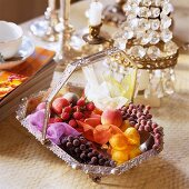 A silver basket of artificial fruits in front of a table lamp with crystal decoration