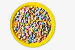 Colorful Conversation Hearts on a Divided Yellow Plate; From Above; White Background