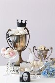 Glasses and old trophies filled with meringues, nougat and pralines