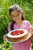 A girl holding a strawberry cake outside