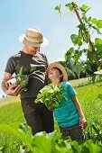 A grandfather and his grandson in a vegetable garden