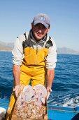 fisherman on boat, presenting the fish