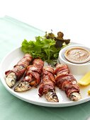 Roasted sardines stuffed with orange slices and wrapped in bacon
