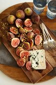 Figs, chopped pistachios and blue cheese on a wooden board