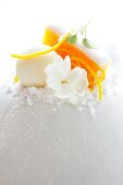 A decoration made with vegetable ice cream, orange zest and a jasmine flower