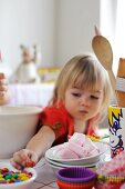 Young girl reaching for sweets from the bowl while baking