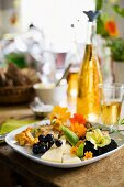 A plate of vegetables, cheese, grapes, mushrooms, mushroom omelette and edible flowers