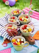 A salad of mozzarella balls and cherry tomatoes on a table outdoors