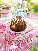 A Nutella birthday cake with candles on a table outdoors