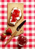 A slice of bread topped with cream cheese and strawberry jam