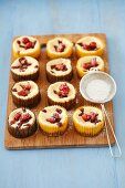 Mini cheesecakes with wild strawberries and icing sugar