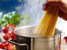 Spaghetti being added to a pot of boiling water