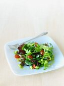 Mixed Green Salad with Edamame on a Plate with a Fork