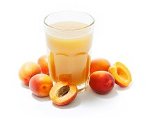 A glass of apricot juice surrounded by whole and halved apricots