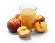 A glass of peach juice surrounded by whole and halved peaches