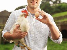Bauer hält Ei und Henne