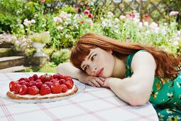 young woman looking at strawberry tart.