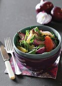 A salad with roasted red onions, grapefruit and rocket