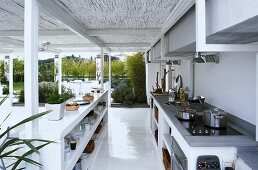 A covered, open plan kitchen with a view of the garden