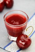 A glass of cherry juice with a fresh cherry